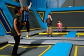 Boy jumping on trampolines and parent celebrating