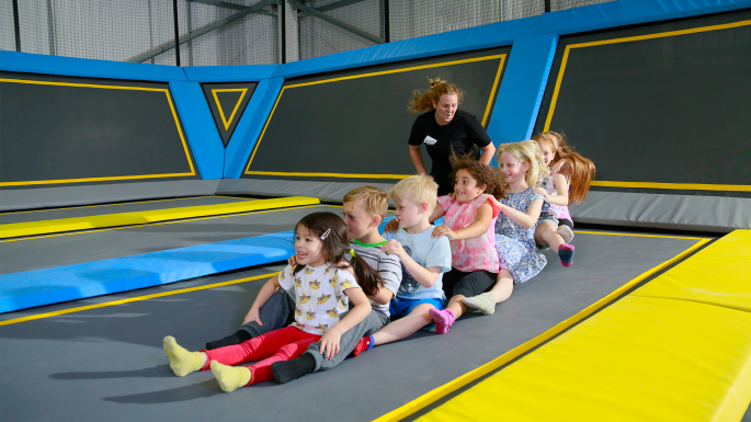 Kids at a party bouncing on a trampoline