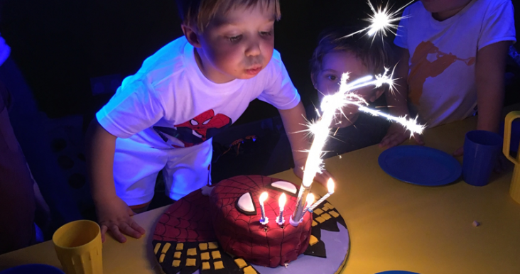 A kid blowing out a spiderman cake at an Oxygen kids birthday party