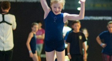 Girl smiling as she jumps on a trampoline