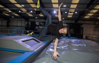 Boy jumping at trampoline park DJ party