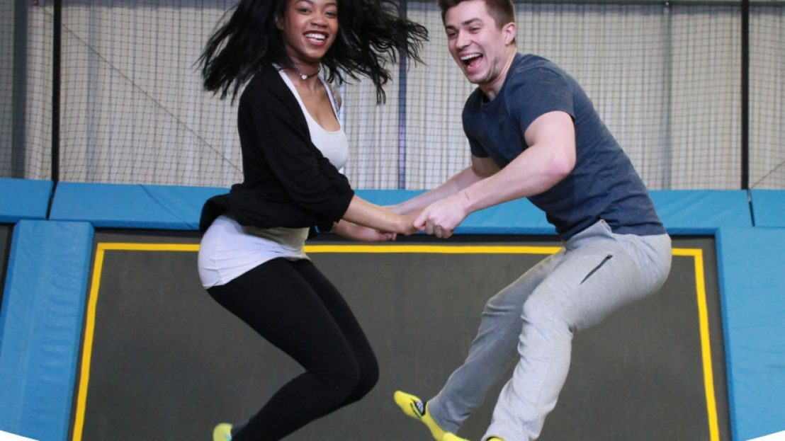 two people jumping on a trampoline holding hands