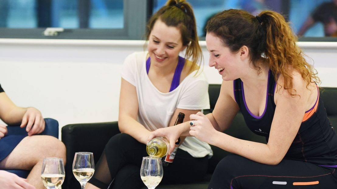 Two girls at corporate event laughing and pouring wine